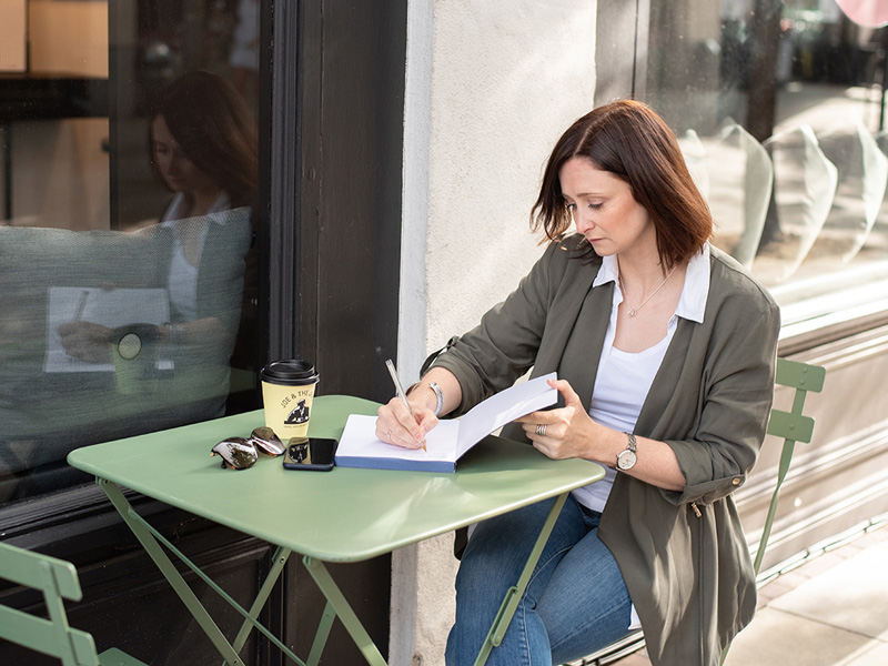 Sophie writing exercise plan at cafe table